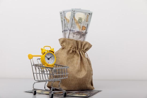 노란색 알람 시계와 달러 돈 가방. 사업 전략 및 투자.