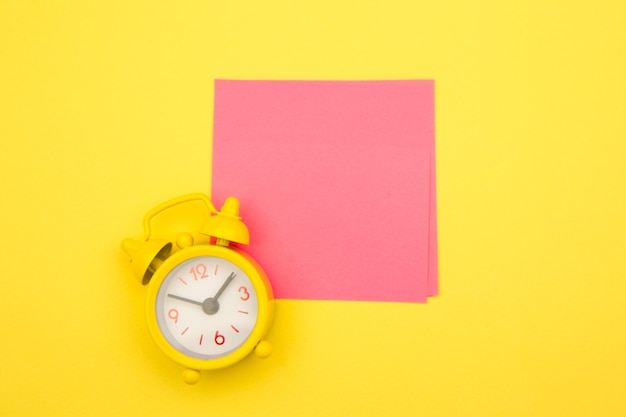 노란색 알람 시계와 노란색에 다채로운 스티커 메모.