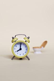黄色の目覚まし時計と白いトイレットボウル