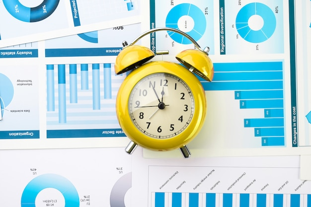 Yellow alarm clock on business charts. business development concept.