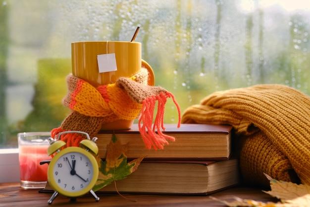 Желтый будильник, чашка на книгах у окна