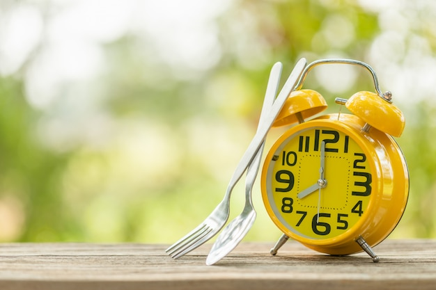 Yellow alarm clock, fork, and spoon on wooden table with green outdoor nature blur  eight o'clock, time for eating concept