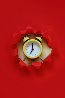 Yellow alarm clock from the paper hole