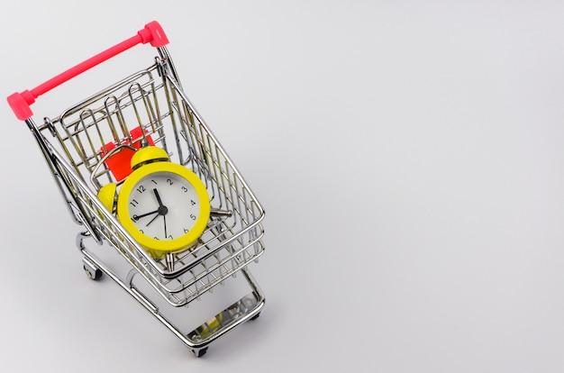 Желтый будильник в тележке для покупок