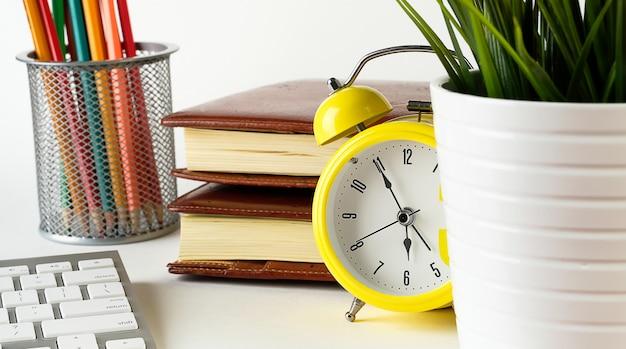 白いテーブルにレトロなスタイルの黄色の目覚まし時計。その隣には鍋の中の花、コップの中の色鉛筆、コンピューターのキーボード、そしてノートブックがあります。フリーランサーまたはビジネスマンのデスクトップ。