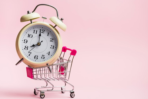 Yellow alarm clock inside the miniature shopping trolley against pink background