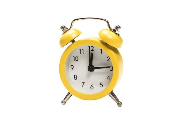 白い表面に分離された黄色の目覚まし時計