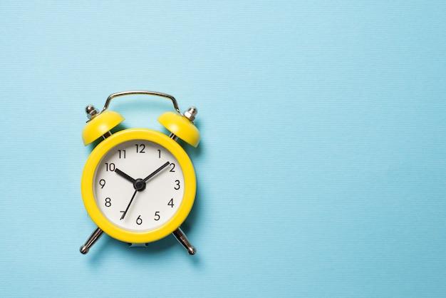 Желтый будильник на синем фоне. скопируйте пространство. концепция времени.