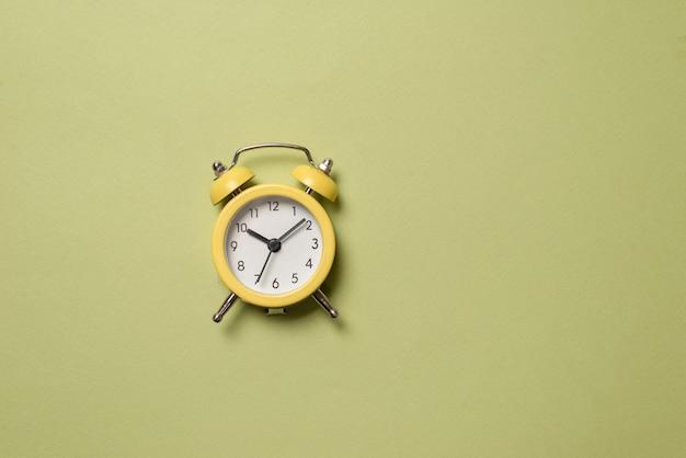 Желтый будильник на зеленом фоне. скопируйте пространство. концепция времени.