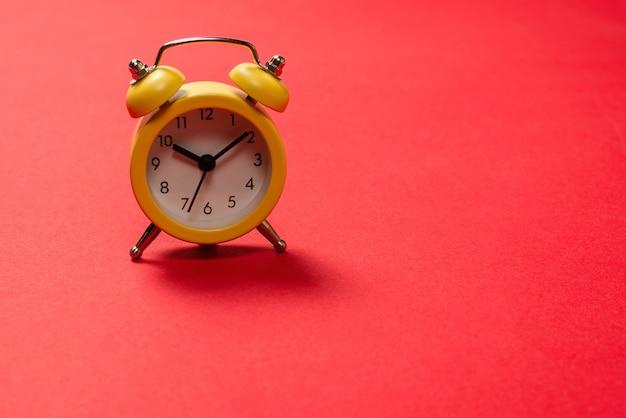 Желтый будильник на красном фоне. скопируйте пространство. концепция времени. скопируйте пространство.