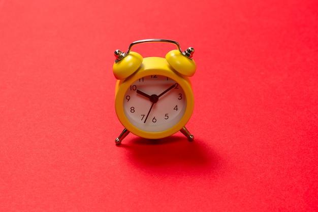 Желтый будильник на красном фоне. скопируйте пространство. концепция времени.