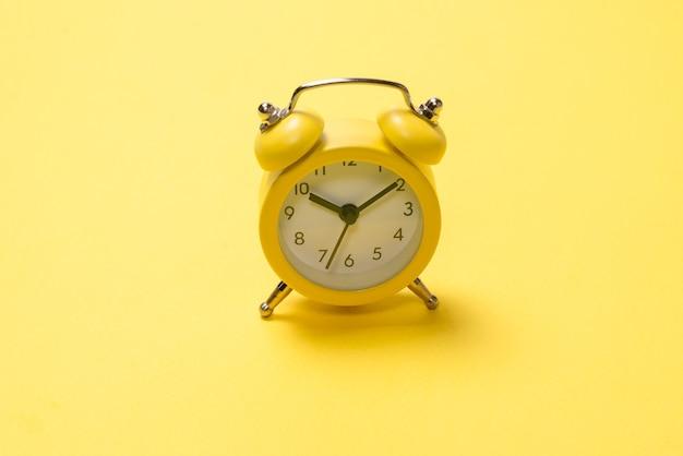Желтый будильник на желтом фоне. скопируйте пространство. концепция времени.