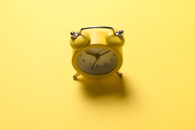 Желтый будильник на желтом фоне. концепция времени.