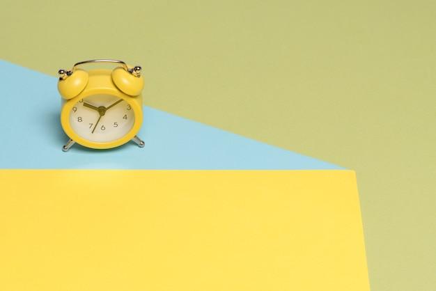 Желтый будильник на желтом, синем и зеленом фоне. скопируйте пространство. концепция времени.
