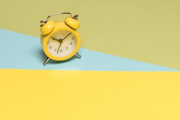 Желтый будильник на желтом, синем и зеленом фоне. скопируйте пространство. концепция времени. Premium Фотографии