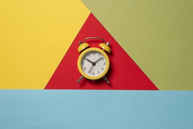 Желтый будильник на желтом, синем, красном и зеленом фоне. скопируйте пространство. концепция времени.