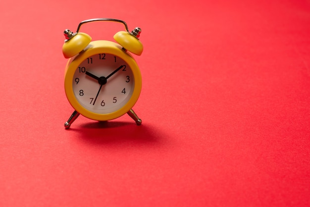 Yellow alarm clock on a red background. copy space. time concept. copy space.