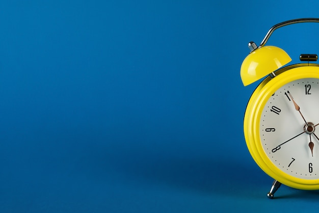Yellow alarm clock in retro style