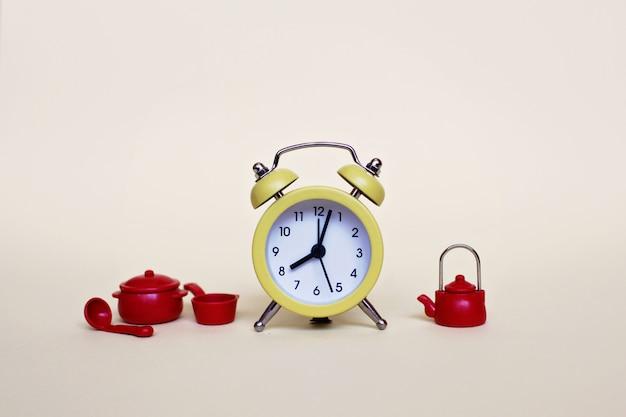 Yellow alarm clock and set of red pans and tea-pot