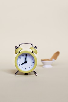 Yellow alarm clock and white toilette bowl