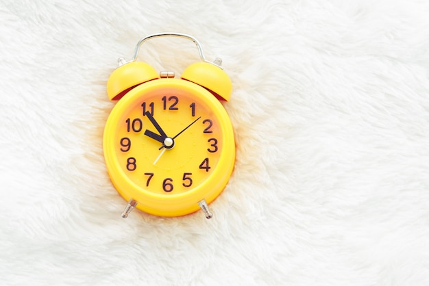Yellow alarm clock on white wool. late and lazy time concept