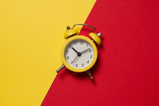 Yellow alarm clock on a yellow, blue, red and green background. copy space. time concept.
