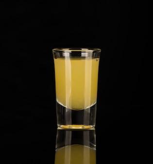 어두운 배경에 격리된 유리잔에 담긴 노란색 알코올