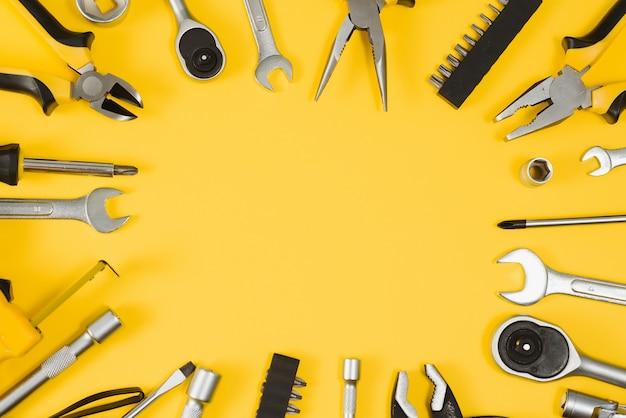 Желтые и черные удобные инструменты (штабелеры и отвертка), изолированные на желтом фоне