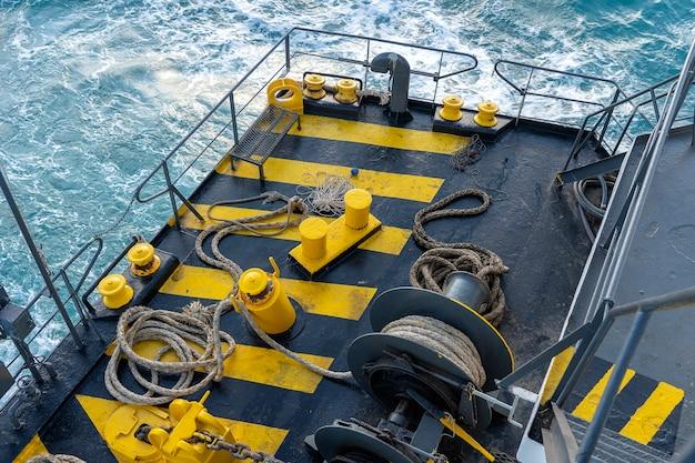 Палубный паром, окрашенный в желтый и черный цвета, с толстым швартовным канатом и синей морской волной