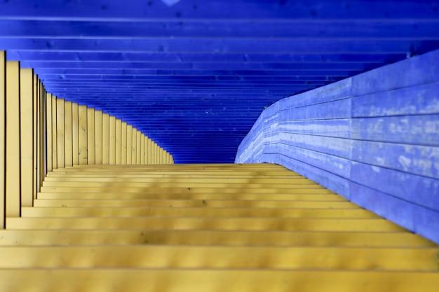 노란색과 파란색 개요입니다. 뒤틀린 다채로운 나무 패널의 구조의 인테리어 디자인 장식. 터널에서 나무 바닥입니다. 건축 배경입니다. 미래의 빈 방에 홀 복도입니다.