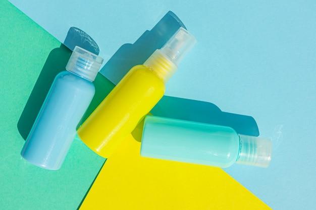同じ色のスペースに黄色と青の化粧品ボトル。有機エッセンス、美容、健康製品のスタイリッシュなコンセプト。コピースペース、ミニマリズム、フラットレイアウト。