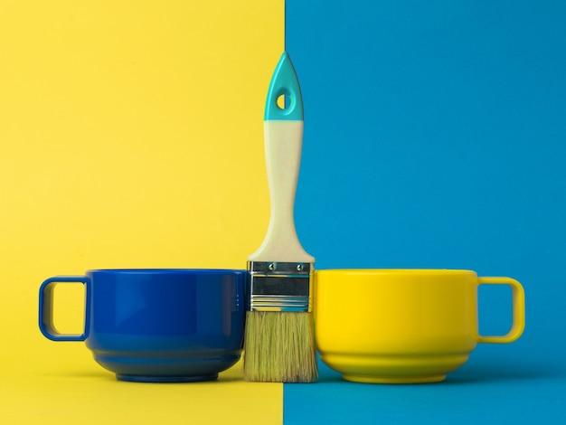 ツートンカラーの背景にブラシで黄色と青のカップ。カラートレンド。