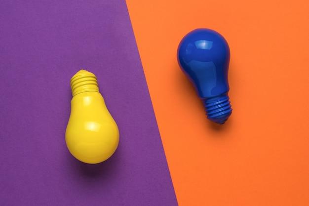 黄色とオレンジ色の背景に黄色と青の電球。ミニマリズム。フラットレイ。