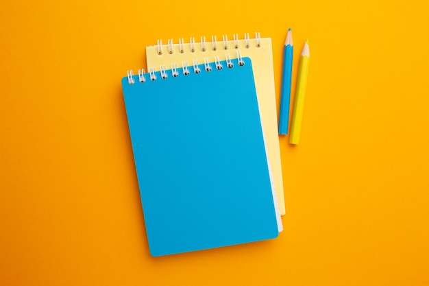 Желто-синий блокнот с карандашами на желтом фоне с местом для надписи