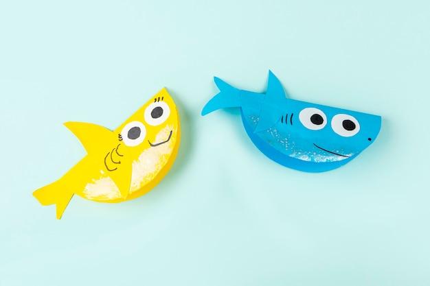 Желтые и синие бумажные акулы на голубом фоне
