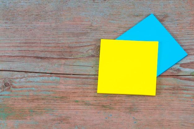 나무 배경에 텍스트를 위한 빈 공간이 있는 노란색 및 파란색 스티커 메모.