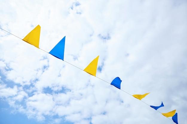 Желтые и синие треугольные фестивальные флаги на фоне неба. праздничная вечеринка на открытом воздухе