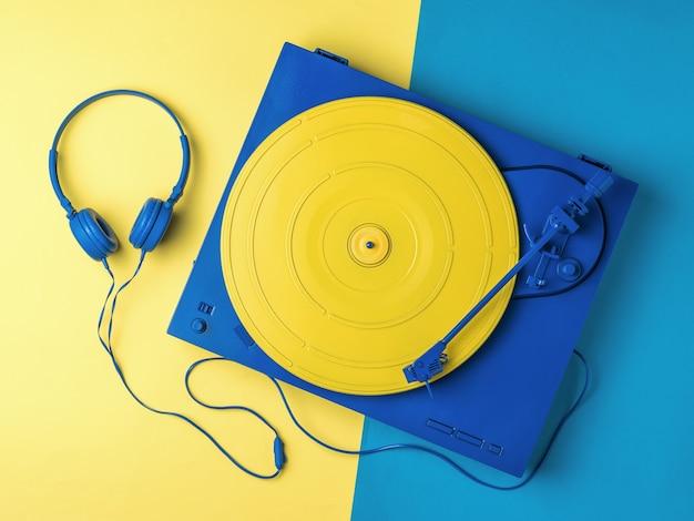 ツートンカラーの背景に黄色と青のビニールレコードプレーヤーとヘッドフォン。レトロな音楽機器。