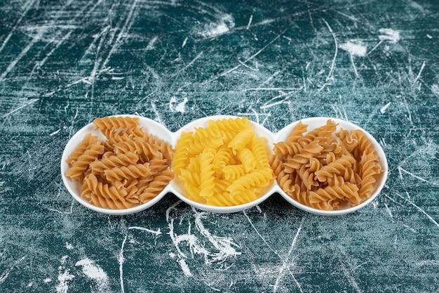 Желтые и коричневые сырые макаронные изделия фузилли в белых мисках.