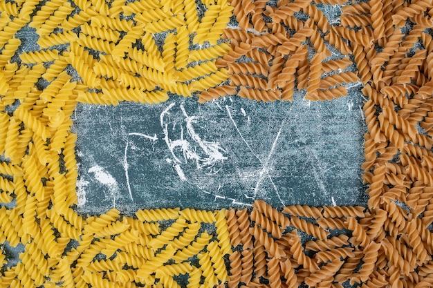 Желтые и коричневые сырые макаронные изделия фузилли на синем фоне. фото высокого качества