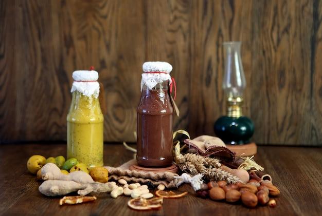 Желтый и шоколадный смузи в бутылке. красочный напиток молочный коктейль со свежими овощами и орехами