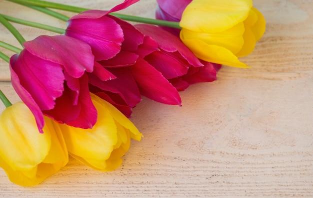 밝은 나무 배경에 노란색과 어두운 핑크 튤립 꽃다발