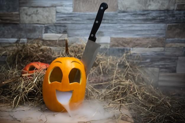 머리에 칼을 꽂고 입에서 연기나 증기가 나는 노란색과 재미있는 할로윈 호박