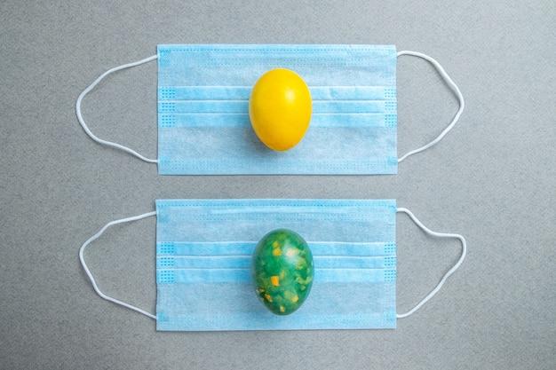 黄色と緑のイースターエッグは、灰色の背景の青い医療マスクの上にあります