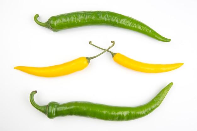 Желтый и зеленый острый перец чили на белой тарелке