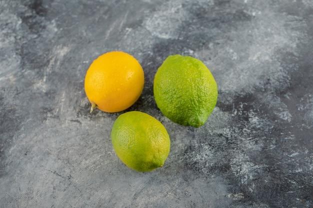 大理石の表面に黄色と緑のレモン。