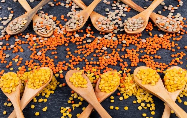 黒い石のテーブルに木製のスプーンで黄色と緑のレンズ豆。ハイアングル。