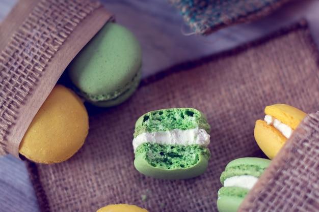 黄麻布を詰めた箱に入った黄色と緑のマカロン。これの1つはかまれています