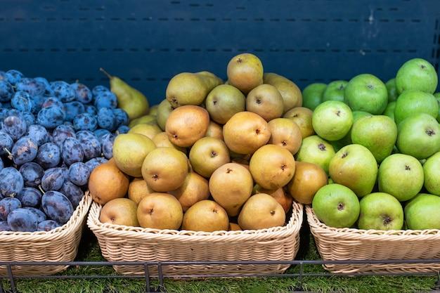 노란색과 녹색 배, 슈퍼마켓의 냉장고 선반에 있는 파란색 자두. 어떤 목적을 위해.
