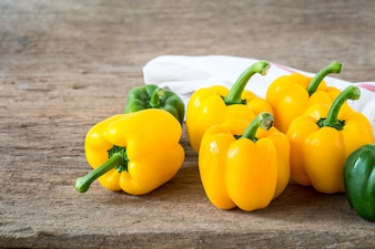 Yellow and green sweet pepper on wooden background